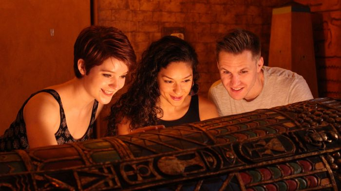Three friends gaze into an open sarcophagus in the Egyptian Tomb escape room at clue chase