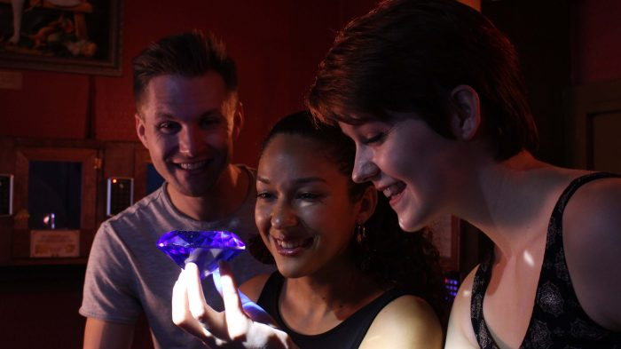 Three friends in clue chase's heist escape room admiring a blue diamond that they've stolen